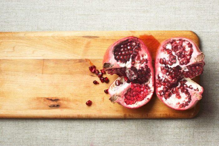 Cut pomegranate on the cutting board.