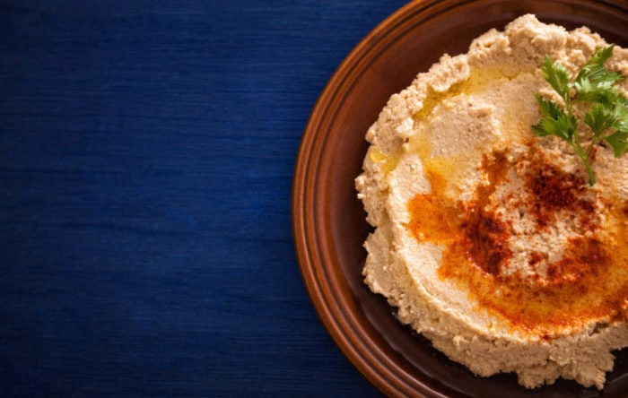 Hummus on a plate with parsley and olive oil on it