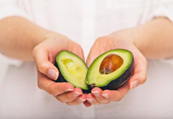 Female hand holding sliced avocado