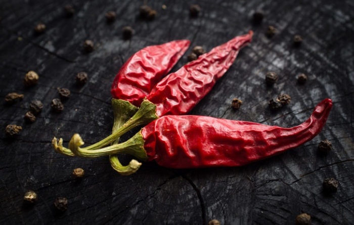 Some hot red peppers and black pepper lie on a dark board