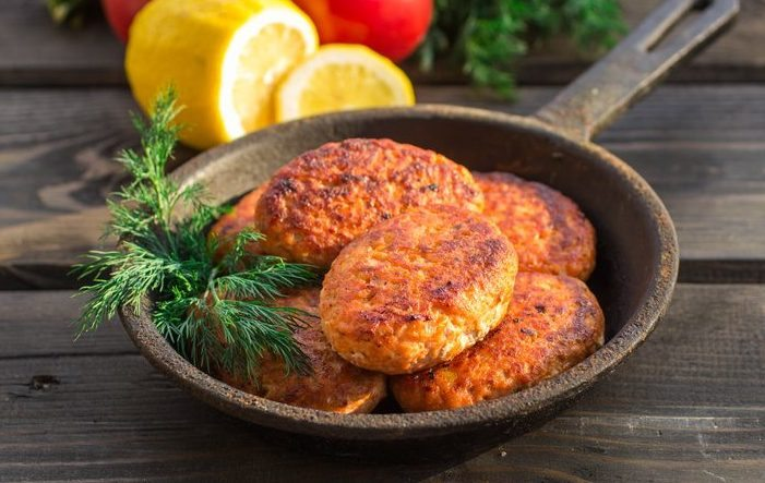 salmon fishcakes in a cast iron skillet, tomatoes and lemon