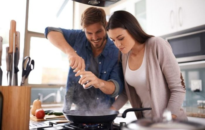 A young couple making dinner together at home