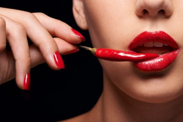 Closeup of a woman holding a red chilli to her mouth