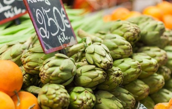 Artichokes for sale on display on a counter